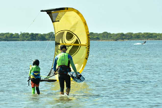 Children are taking kitesurf private lesson in Sicily at Lo Stagnone lagoon with Flow Kite School.