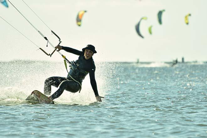 Der Schüler der Flow Kite School fährt mit einer Hand auf der Bar windaufwärts.